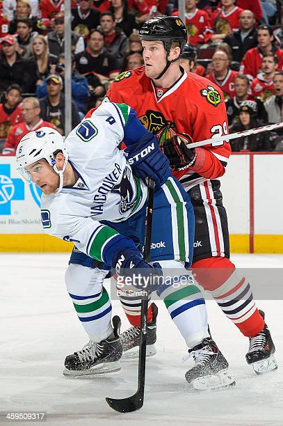 Yannick Weber of the Vancouver Canucks and Bryan Bickell of the Chicago Blackhawks watch for the puck during the NHL game on December 20 2013 at the...