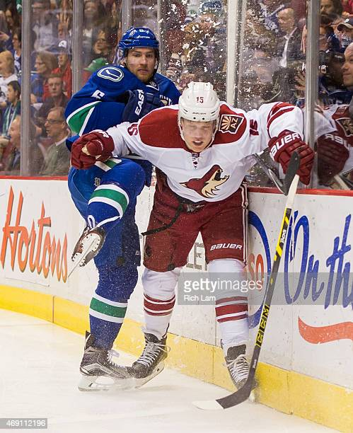 Yannick Weber of the Vancouver Canucks and Henrik Samuelsson of the Arizona Coyotes collide along the end boards in NHL action on April 2015 at...