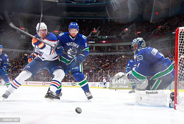 Yannick Weber of the Vancouver Canucks checks Jesse Joensuu of the Edmonton Oilers in front of Roberto Luongo of the Canucks during their NHL game at...