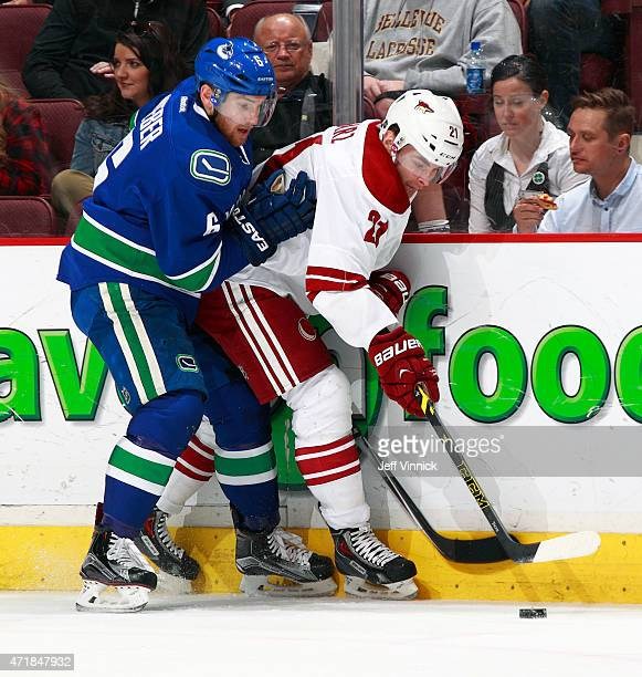 Yannick Weber of the Vancouver Canucks checks Jordan Szwarz of the Arizona Coyotes during their NHL game at Rogers Arena April 9 2015 in Vancouver...