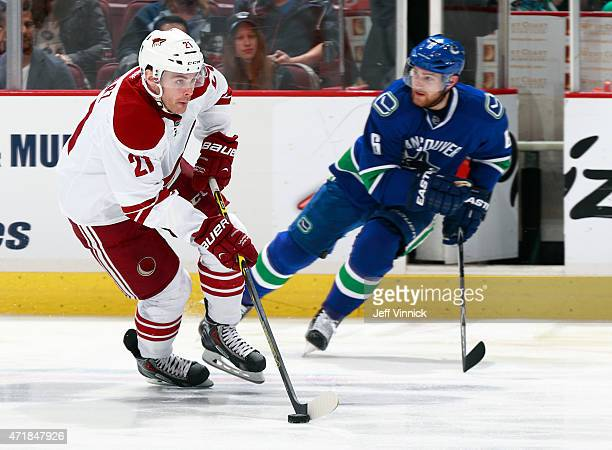 Yannick Weber of the Vancouver Canucks looks on as Jordan Szwarz of the Arizona Coyotes skates up ice with the puck during their NHL game at Rogers...