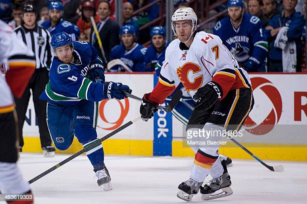 Yannick Weber of the Vancouver Canucks takes a shot on net while TJ Brodie of the Calgary Flames checks on January 18 2014 at Rogers Arena in...