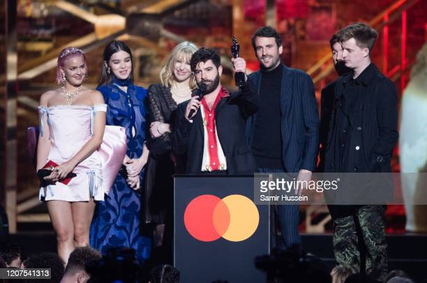 Yannis Philippakis Jack Bevan Jimmy Smith and Edwin Congreave of the band Foals accept the Best Group award from AnneMarie Hailee Steinfeld and...