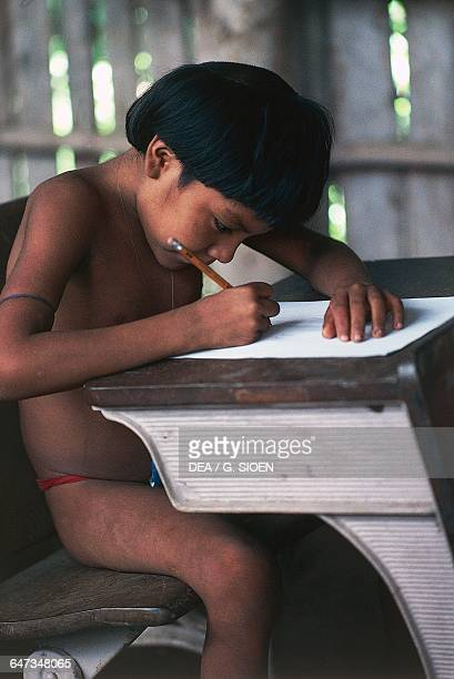Yanomami child writing on a school bench The Amazon rainforest Venezuela