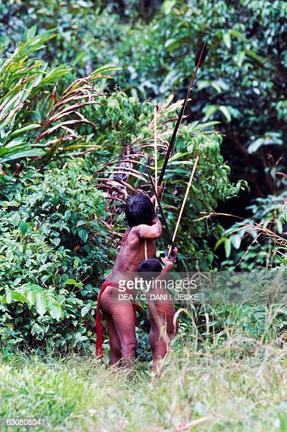 Yanomami man and children from the Cavaroa tribe hunting in the forest with their bow and arrows near the Siapa River Amazonas Guyana Venezuela