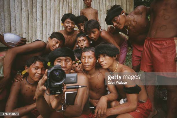 A Yanomami man is watched by teenagers as he films with a video camera at a mission school in the Amazon rainforest of Venezuela 2001