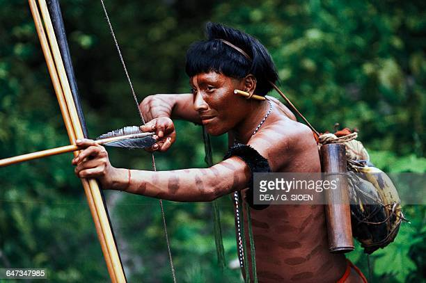 Yanomami man taking aim with a bow and arrow The Amazon rainforest Venezuela