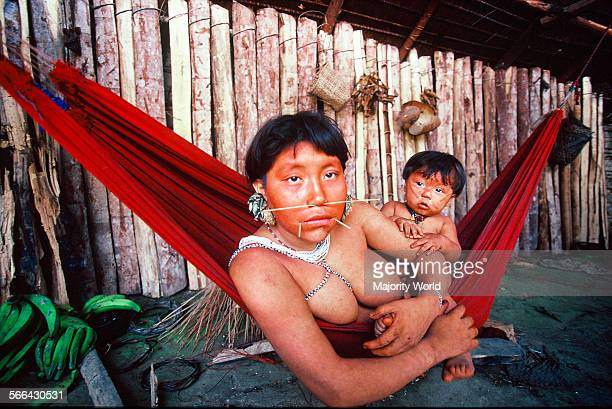 A Yanomami mother with her child on a chinchorro Chinchorros are used to take rest to sleep to play with their children and also seat over while...