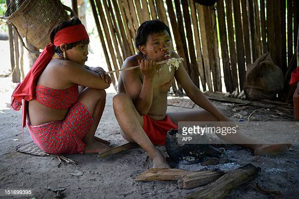 A Yanomami native man eats next to his wife at the Irotatheri community Amazonas state southern Venezuela 19 km away from the border with Brazil on...