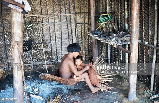 Yanomami woman with a baby on her lap building a straw basket inside a hut Mato Grosso Brazil