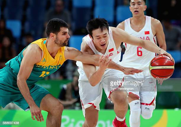 Yanyuhang Ding of China drives down court against Kevin Lisch of Australia during the Men's Basketball Preliminary Round Group A China vs Australia...