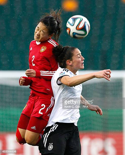 Yao Lingwei of China PR battles for a header against Kathrin Schermuly of Germany at Commonwealth Stadium on August 8 2014 in Edmonton Canada