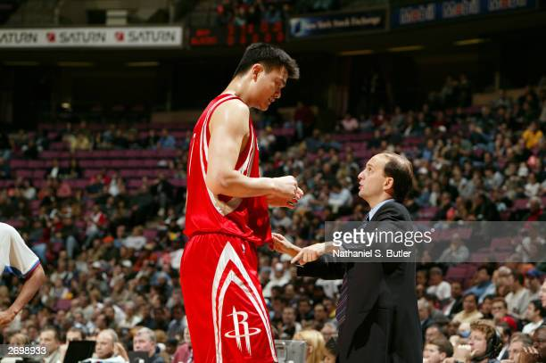 Yao Ming and Coach Jeff Van Gundy of the Houston Rockets talk against the New Jersey Nets during NBA action on November 4 2003 at Continental...