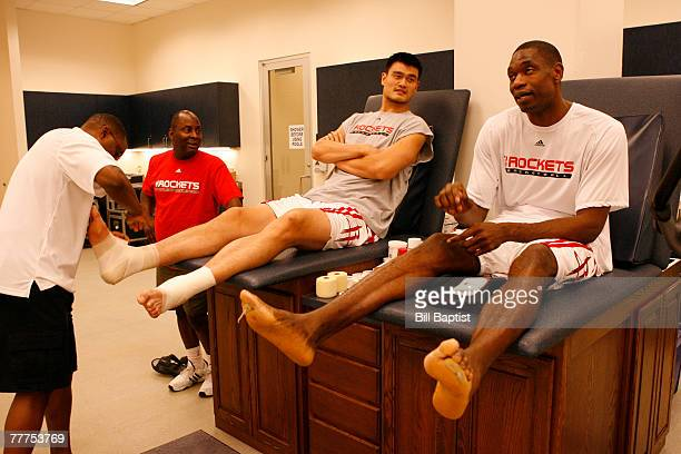 Yao Ming and Dikembe Mutumbo of the Houston Rockets talk while getting their feet taped before a game against the San Antonio Spurs November 6 2007...