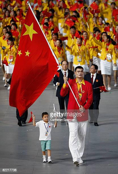 Yao Ming of the China Olympic men's basketball team carries his country's flag to lead out the delegation accompanied by Lin Hao, a 9-year old...