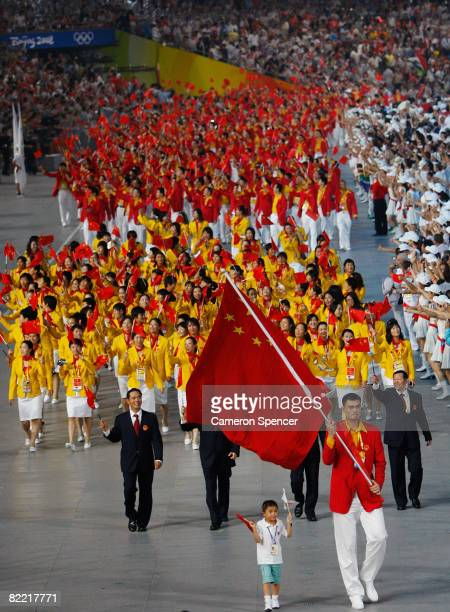 Yao Ming of the China Olympic men's basketball team carries his country's flag to lead out the delegation accompanied by Lin Hao a 9year old...