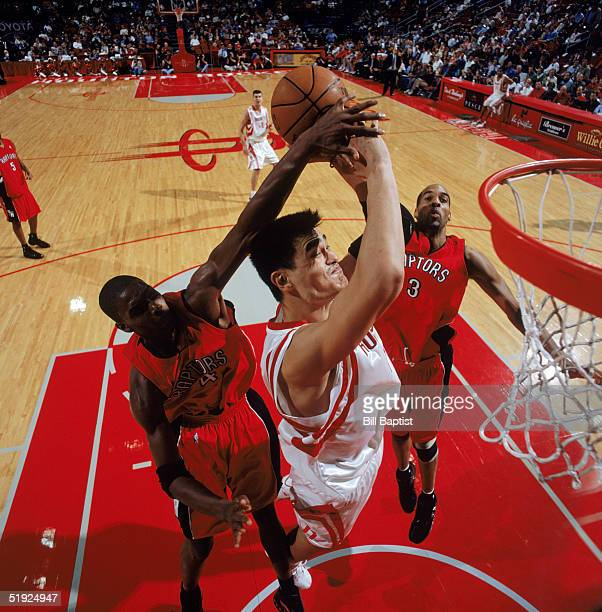 Yao Ming of the Houston Rockets gets blocked as he take the ball to the basket against Chris Bosh and Loren Woods of the Toronto Raptors at Toyota...