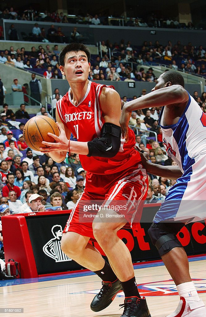 Yao Ming #11 of the Houston Rockets moves the ball against Elton Brand #42 of the Los Angeles Clippers during the game at Staples Center on November 20, 2004 in Los Angeles, California. The Rockets won in overtime 91-86.