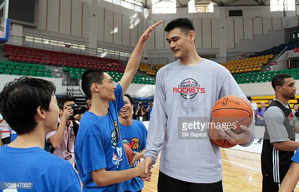 Yao Ming of the Houston Rockets plays basketball with deaf children during a NBA Cares event on October 15 2010 at Guangzhou Sports University Gym in...