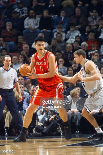 Yao Ming of the Houston Rockets posts up Radoslav Nesterovic of the San Antonio Spurs during the game at the SBC Center on December 13, 2003 in San...