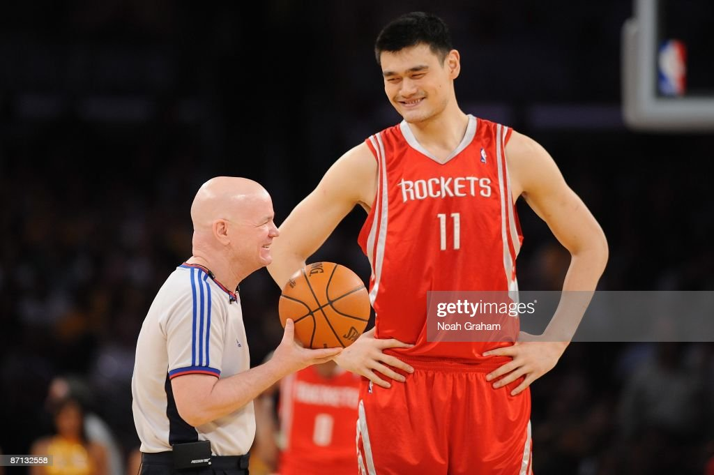 yao ming of the houston rockets shares a laugh with referee joe
