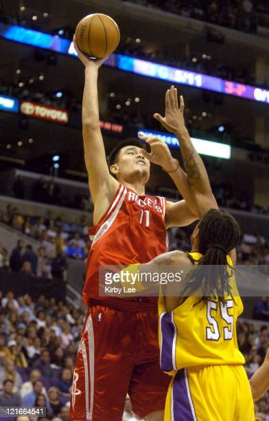 Yao Ming of the Houston Rockets shoots over Brian Grant of the Los Angeles Lakers during the NBA game between the Los Angeles Lakers and the Houston...