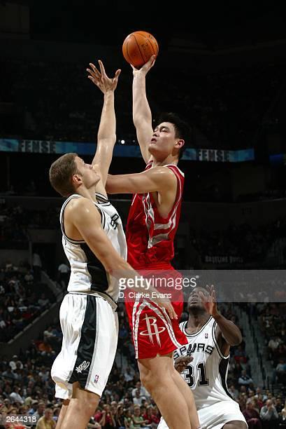 Yao Ming of the Houston Rockets shoots over Rasho Nesterovic of the San Antonio Spurs in NBA preseason action at the SBC Center in San Antonio Texas...