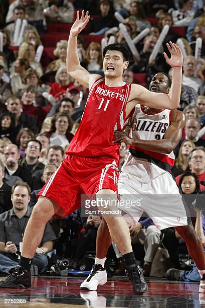 Yao Ming of the Houston Rockets waits for a pass as Dale Davis of the Portland Trail Blazers defends in a game on November 21 2003 at the Rose Garden...