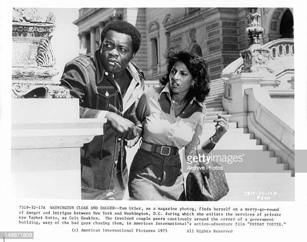 Yaphet Kotto and Pam Grier look cautiously around the corner of a government building in a scene from the film 'Friday Foster' 1975