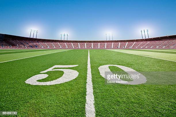 50 yard line on football field in stadium. - american football pitch stock pictures, royalty-free photos & images