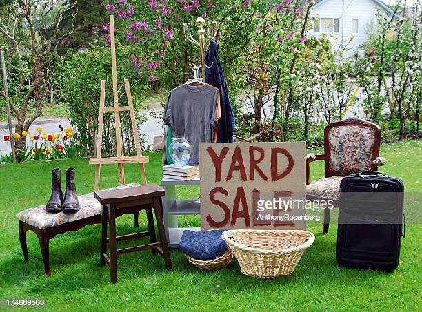 Yard sale sign on a lawn with various items