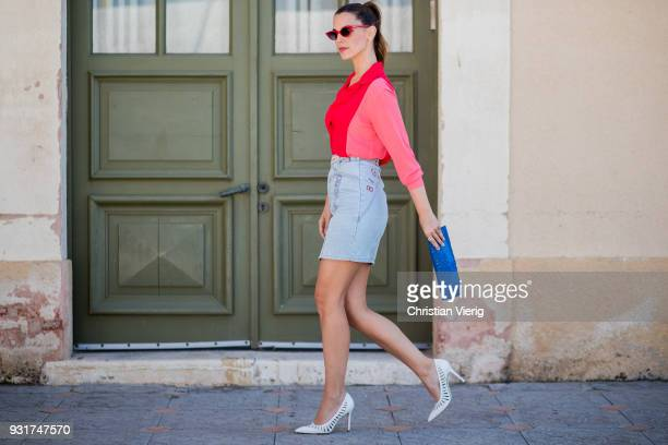 Yarden Harel wearing denim skirt red blouse white pumps clutch is seen during Tel Aviv Fashion Week on March 13 2018 in Tel Aviv Israel