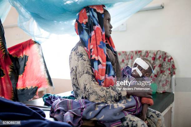 Yariy Bule holds her daughter Farhiyo Yussuf age 3 who is severely malnourished in a hospital in the IFOR refugee camp on July 28 2011 outside Dadaab...