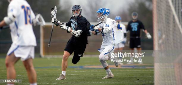 Yarmouth's Gavin Hamm looks for a shot under pressure from Falmouth's Riley Reed