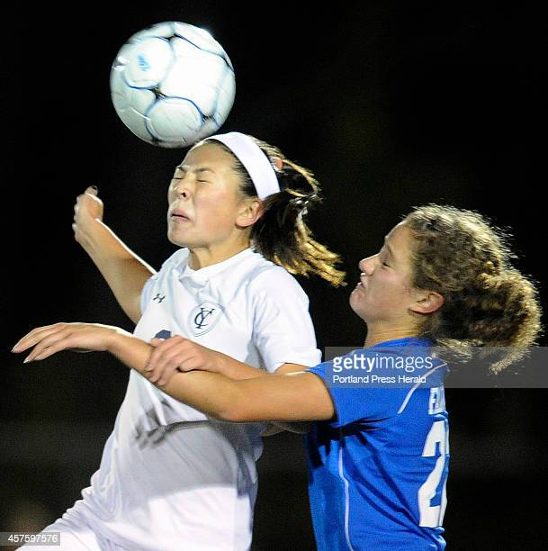 Yarmouth's Lane Simsarian left connects with the ball for a header as she fends of Marcy Kittredge at right during a girls soccer game in Yarmouth...