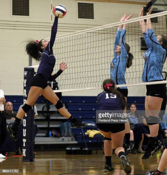 Yarmouth's Marie Leblanc spikes the ball as Windham's Kaitlyn Gedicks center and Meghan Harmon defend during the match in Yarmouth on Thursday...
