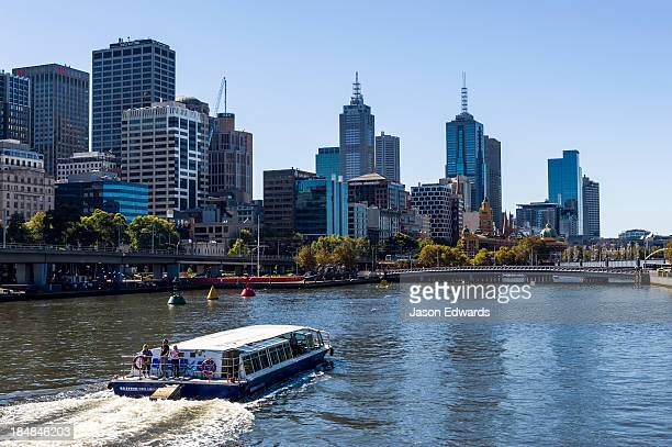A water taxi carries tourists sightseeing along the Yarra River.