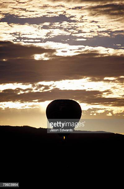 The silhouette of a Hot Air Balloon and jet flame at dawn.