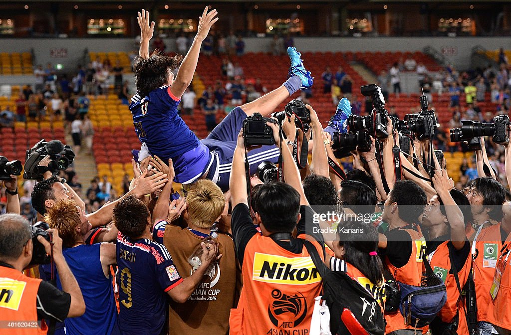 Yashuhito Endo of Japan is thrown into the air by team mates in celebration of his 150th game for Japan during the 2015 Asian Cup match between Iraq and Japan at Suncorp Stadium on January 16, 2015 in Brisbane, Australia.