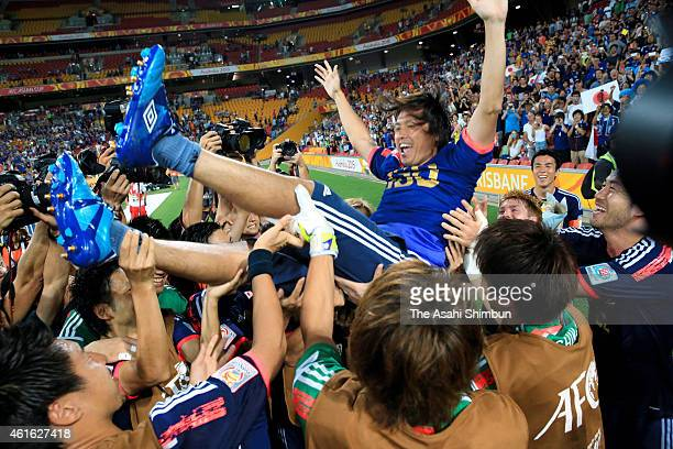 Yashuhito Endo of Japan is thrown into the air by team mates in celebration of his 150th game for Japan after the 2015 Asian Cup Group D match...