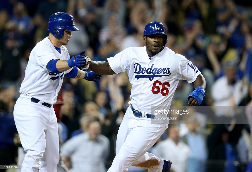 Yasiel Puig #66 and Yasmani Grandal #9 of the Los Angeles Dodgers celebrate after Puig scored the winning run on a walk off single by Howie Kendrick in the ninth inning against the Arizona Diamondbacks at Dodger Stadium on June 10, 2015 in Los Angeles, California. The Dodgers won 7-6.