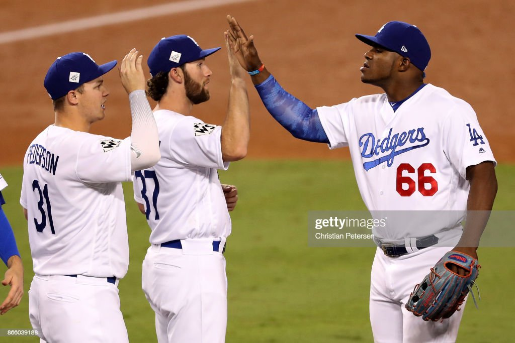 Yasiel Puig #66 (R) high fives Charlie Culberson #37 and Joc Pederson #31 of the Los Angeles Dodgers after defeating the Houston Astros 3-1 in game one of the 2017 World Series at Dodger Stadium on October 24, 2017 in Los Angeles, California.