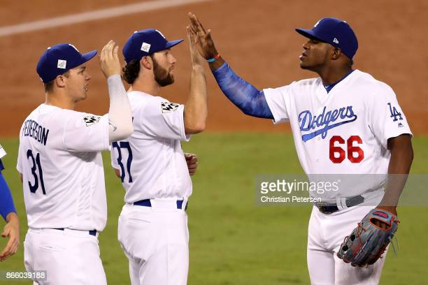 Yasiel Puig high fives Charlie Culberson and Joc Pederson of the Los Angeles Dodgers after defeating the Houston Astros 31 in game one of the 2017...