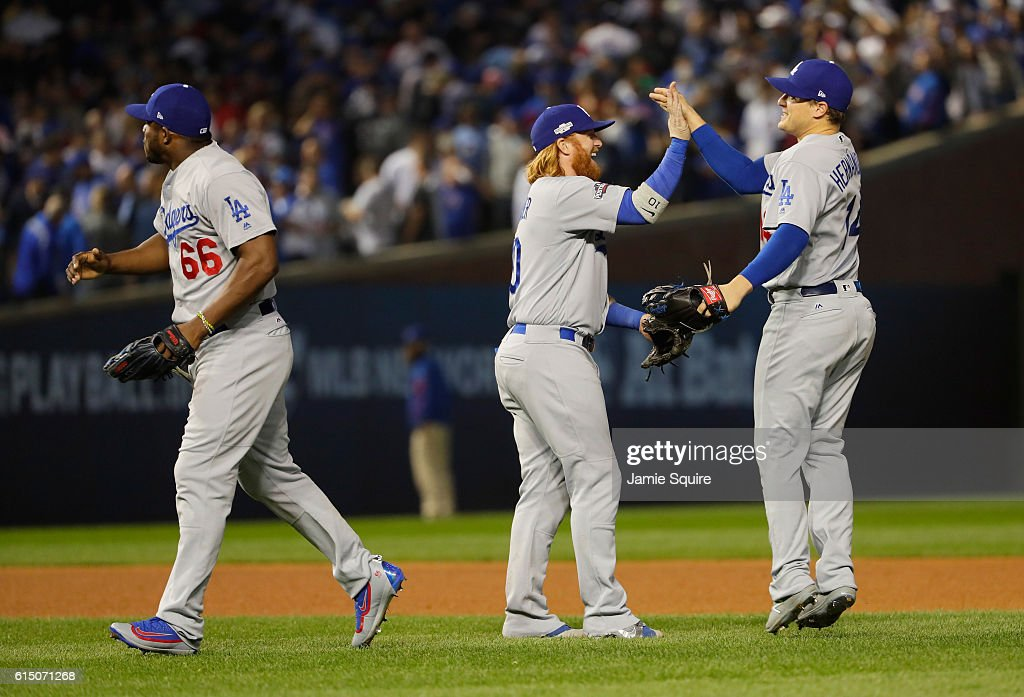 Yasiel Puig #66, Justin Turner #10 and Enrique Hernandez #14 of the Los Angeles Dodgers celebrate after defeating the Chicago Cubs 1-0 in game two of the National League Championship Series at Wrigley Field on October 16, 2016 in Chicago, Illinois.