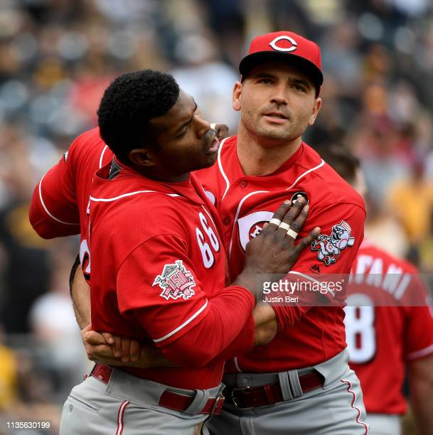 Yasiel Puig of the Cincinnati Reds is restrained by Joey Votto after benches clear in the fourth inning during the game against the Pittsburgh...
