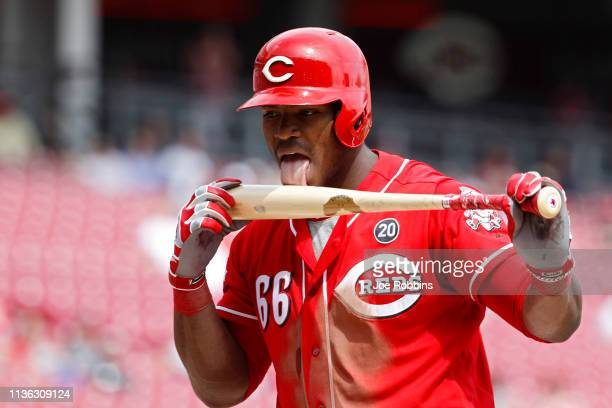 Yasiel Puig of the Cincinnati Reds licks his bat after fouling off a pitch in the seventh inning against the Miami Marlins at Great American Ball...