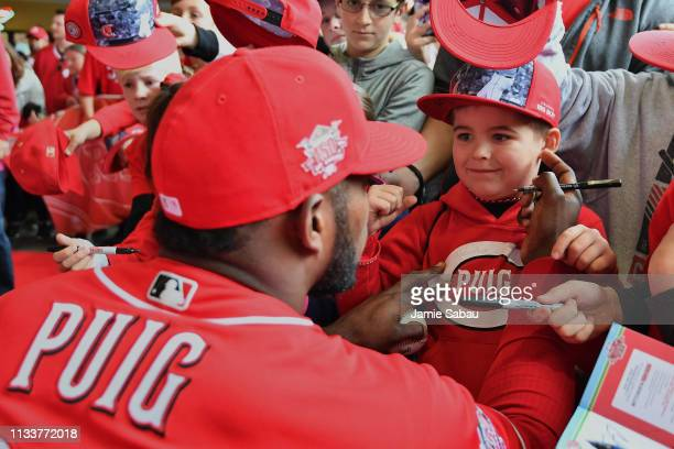 Yasiel Puig of the Cincinnati Reds signs autographs for young fans before a game against the Pittsburgh Pirates as part of Kids Opening Day at Great...