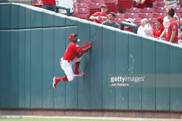 Yasiel Puig of the Cincinnati Reds tries to catch the ball against the right field wall in foul territory in the first inning against the Miami...
