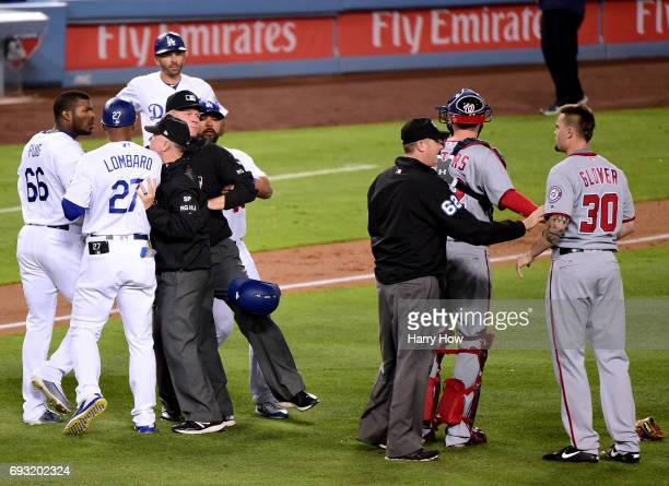 Yasiel Puig of the Los Angeles Dodgers and Koda Glover of the Washington Nationals are restrained from each other following a Puig strikeout to end...