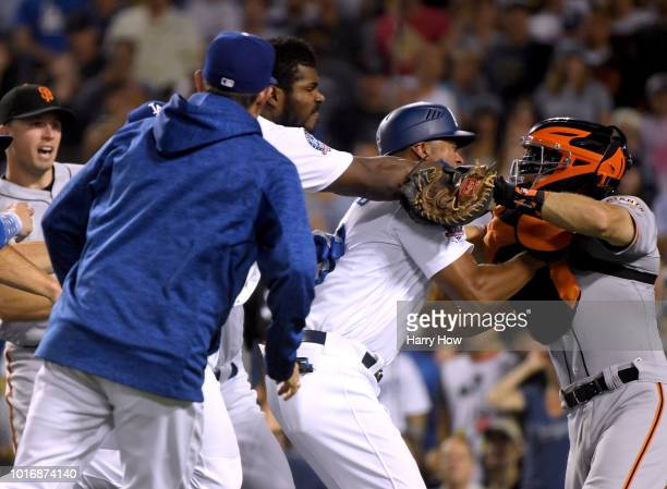 Yasiel Puig of the Los Angeles Dodgers and Nick Hundley of the San Francisco Giants fight as first base coach George Lombard comes between the two...